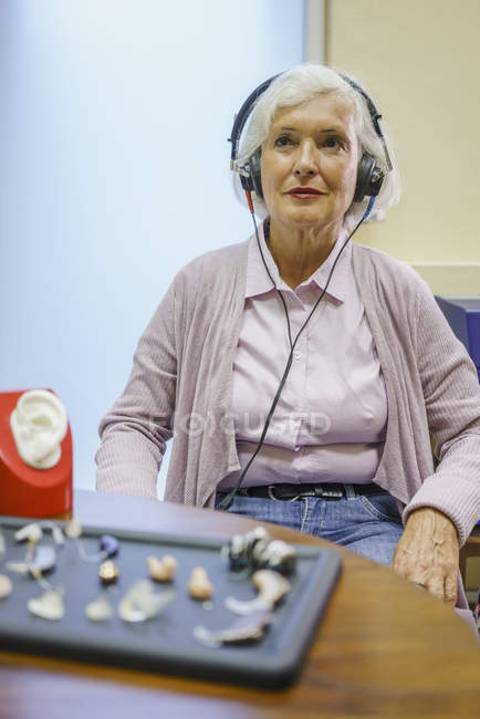 Senior patient wearing headphones during hearing test while sitting at clinic — Stock Photo