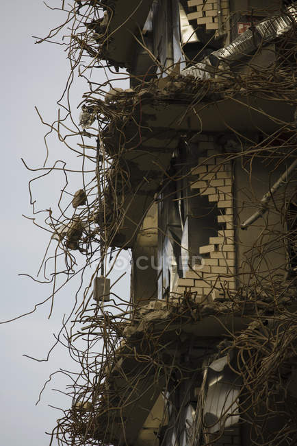 Inquadratura dal basso della facciata dell'edificio demolito sopra il cielo grigio — Foto stock