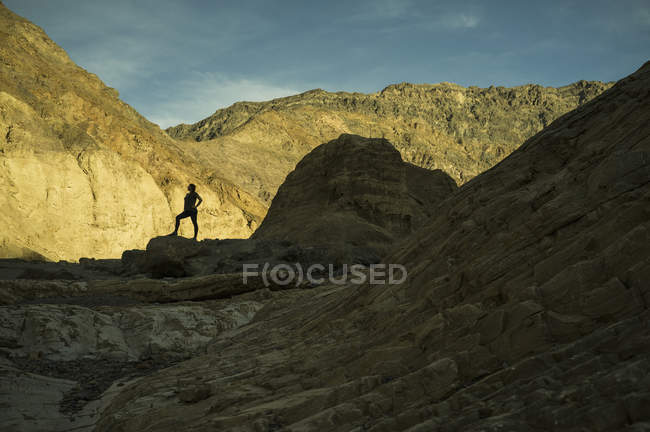 Silhouette of woman standing on cliff against rocky landscape — Stock Photo
