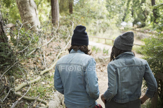 Rear view of couple walking in sunlit park — Stock Photo