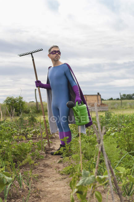 Mature man in superhero costume holding rake and watering can while standing at vegetable garden — Stock Photo