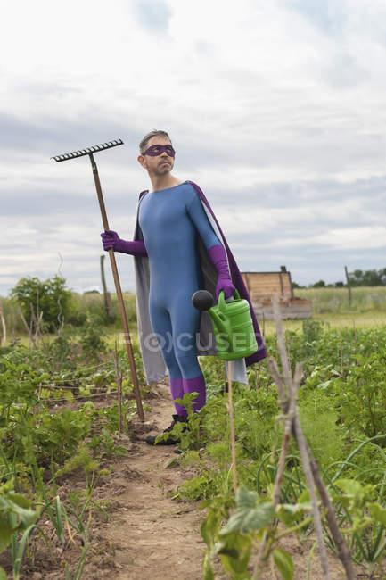 Uomo maturo in costume del supereroe che tiene rastrello e annaffiatoio mentre levandosi in piedi all'orto — Foto stock