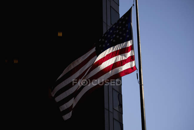 Low angle of waving flag by building in city against clear sky — Foto stock