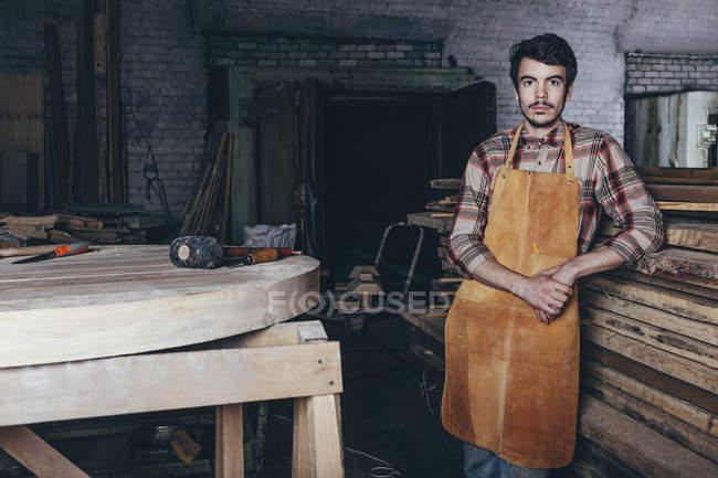 Portrait d'un menuisier debout près d'une pile de bois en atelier — Photo de stock