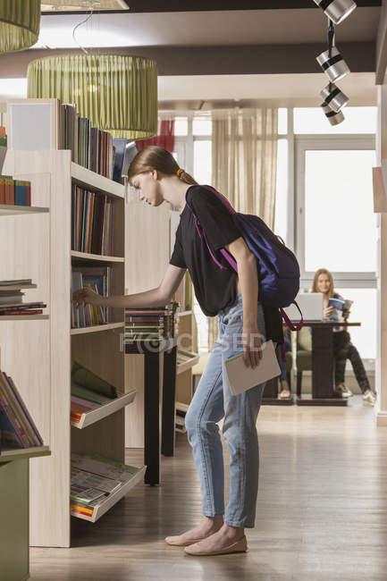 Seitenansicht der Frau auf der Suche nach Buch in Bibliothek — Stockfoto