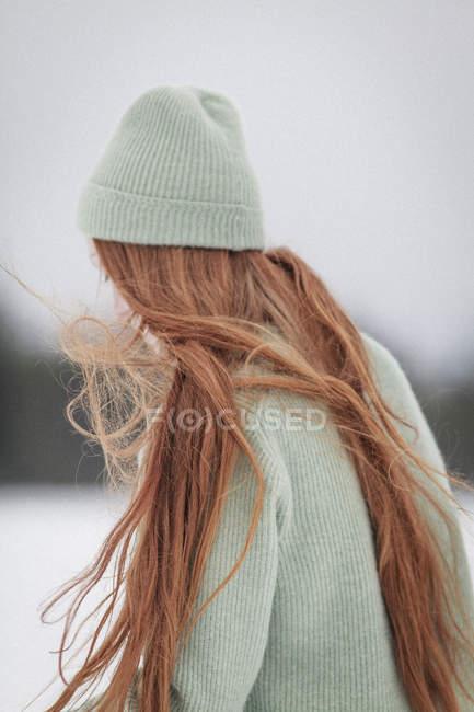 Молодая женщина с длинными рыжими волосами в вязаной шляпе и свитере зимой — стоковое фото