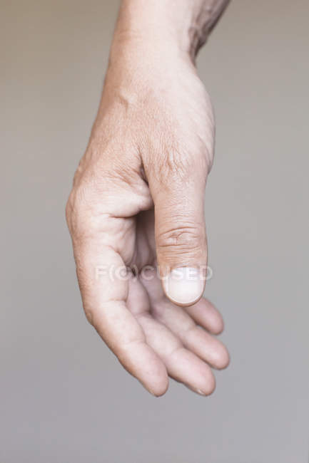Cropped image of hand against gray background — Stock Photo