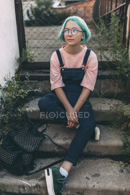 Menina adolescente elegante sentado em passos contra cerca — Fotografia de Stock