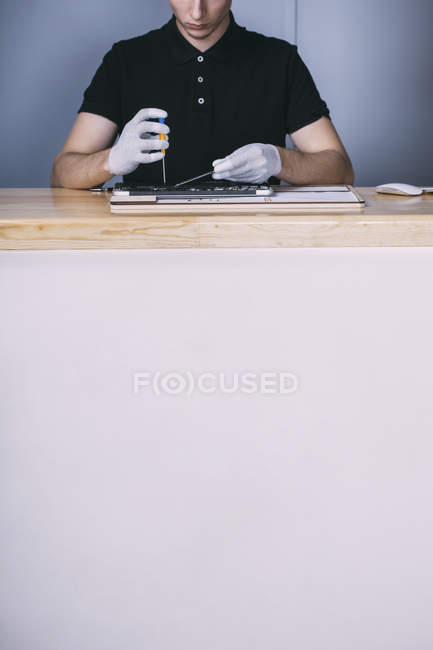 Midsection of young male technician repairing digital tablet at electronics store — Stock Photo