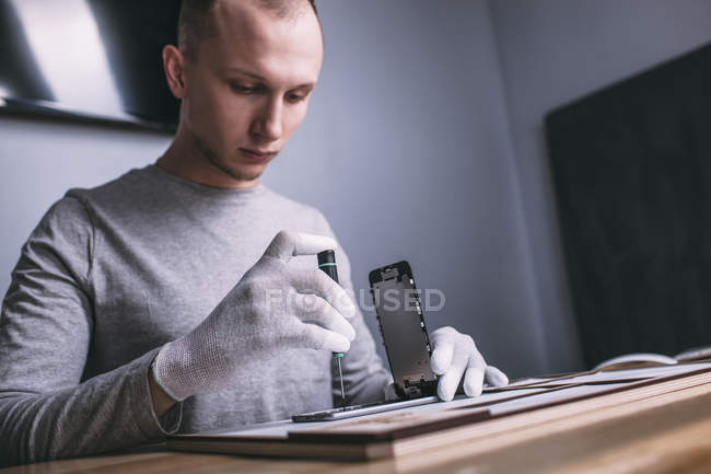 Young male technician repairing smart phone at electronics store — Stock Photo