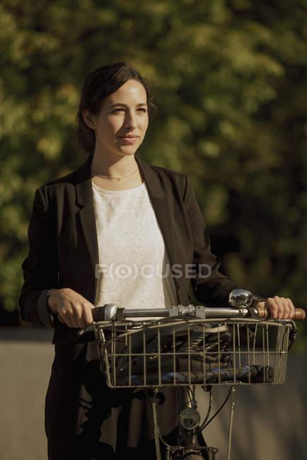 Продуманий бізнес-леді фотографіях хтось дивитися вбік стоячи з велосипеда на сонячний день — стокове фото