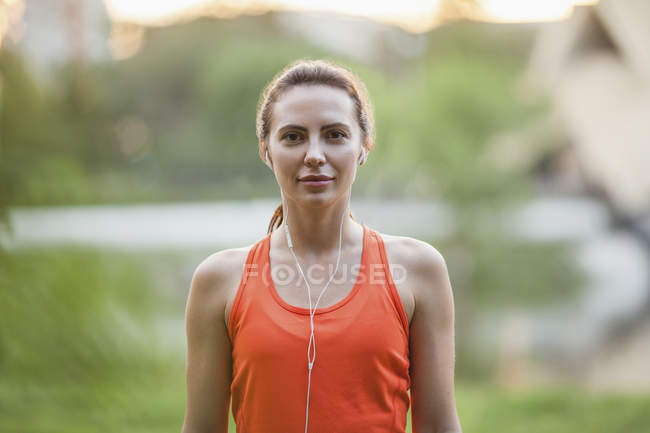 Portrait of sporty young woman with earphones at park — Stock Photo
