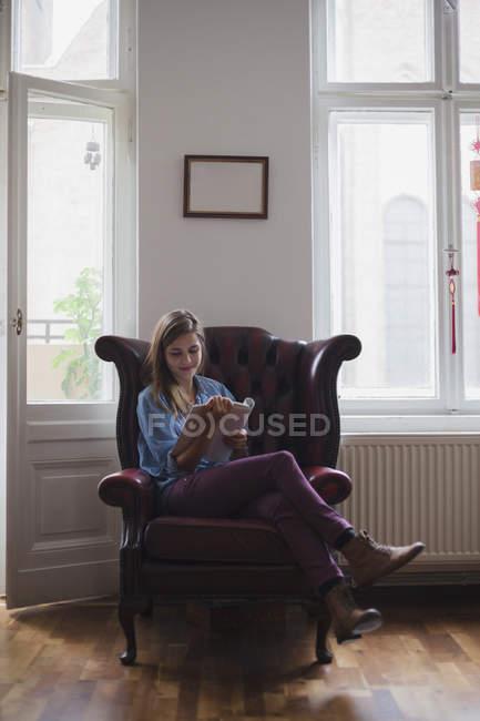 Женский университет студент, сидя в кресле при чтении книги дома — стоковое фото