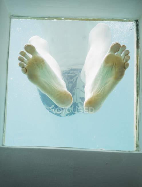 Diretamente abaixo tiro de pés masculinos vistos através de vidro na água — Fotografia de Stock
