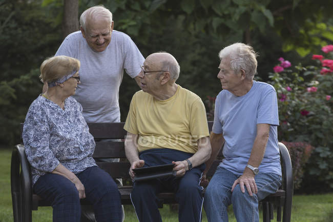 Smiling senior friends talking while using digital tablet at park bench — Stock Photo