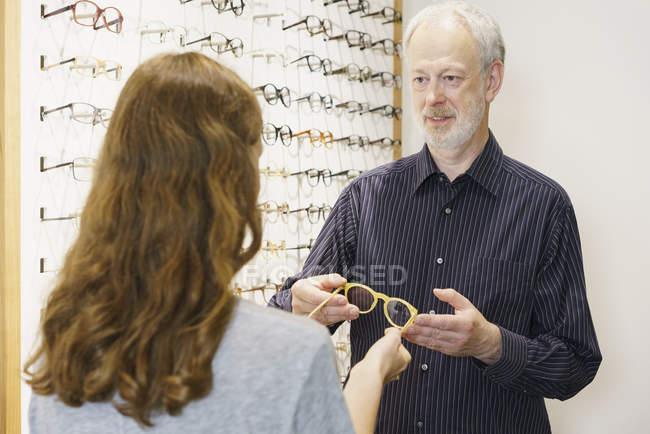 Владелец показывает очки женщине с каштановыми волосами в магазине — стоковое фото