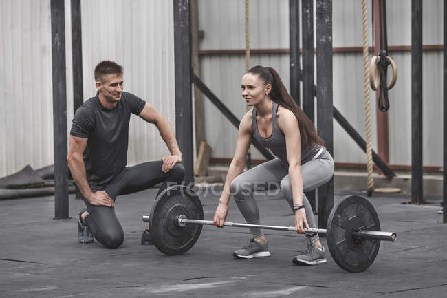 Männliche Lehrer betrachten Sportlerin heben Langhantel beim Crossfit training — Stockfoto