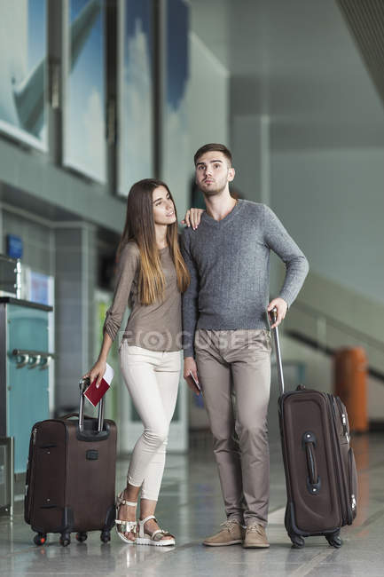 Young couple with luggage waiting at airport — Stock Photo