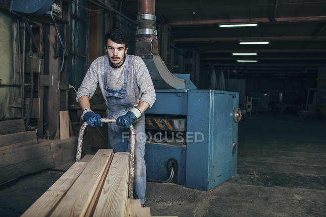 Плотник толкает стопку деревянных досок на тележке в мастерской — стоковое фото