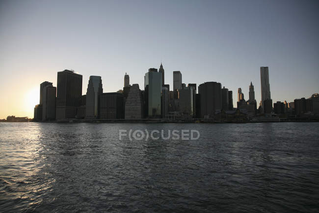 Silhouetted skyline with skyscrapers over sunset sky — Stock Photo