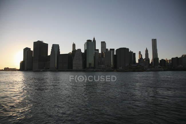 Silhouette der Skyline mit Wolkenkratzern über dem Himmel bei Sonnenuntergang — Stockfoto