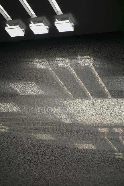 Low angle view of illuminated light on ceiling with reflection over glass — Stock Photo
