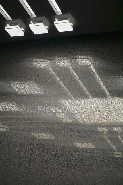 Vista de ângulo baixo de luz iluminado no teto com reflexão sobre vidro — Fotografia de Stock