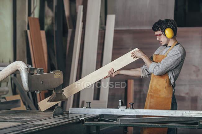 Carpinteiro examinando prancha de madeira perto de serra de mesa na oficina — Fotografia de Stock