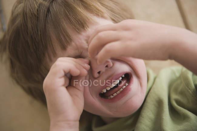 Jeune garçon pleure avec mains couvrant le visage — Photo de stock