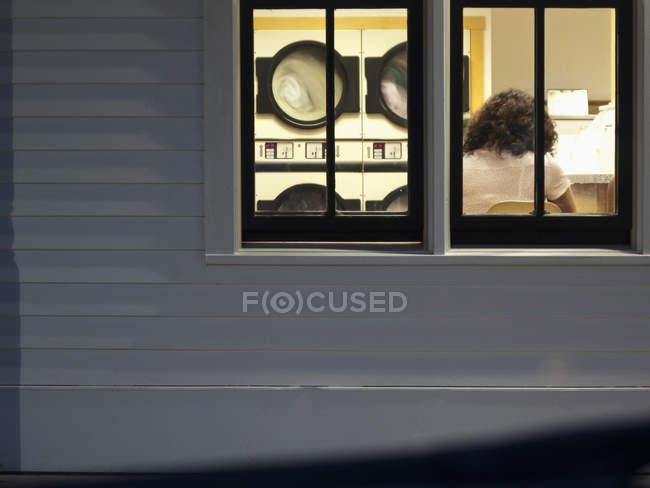 Vista posteriore donna in lavanderia visto attraverso la finestra — Foto stock