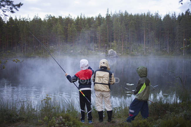 Rear view of children wearing raincoats fishing at lake in foggy weather — Stock Photo