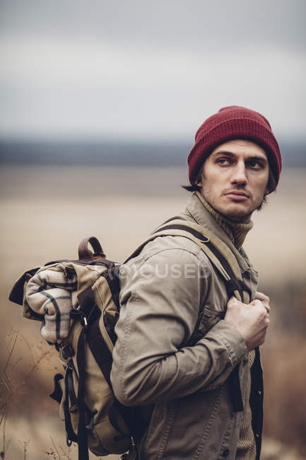 Thoughtful hiker carrying backpack and looking away while standing outdoors — Stock Photo
