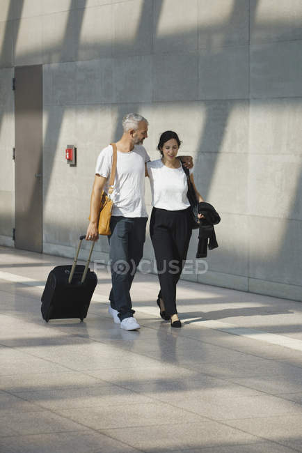 Couple with wheeled luggage talking while walking in airport — Stock Photo