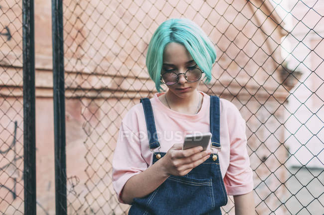 Teenage girl using mobile phone while standing by fence in city — Stock Photo
