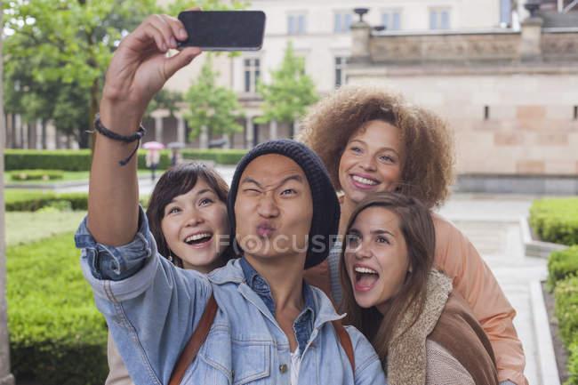 Jeune homme faisant visage tout en prenant selfie avec des amies, Berlin, Allemagne — Photo de stock