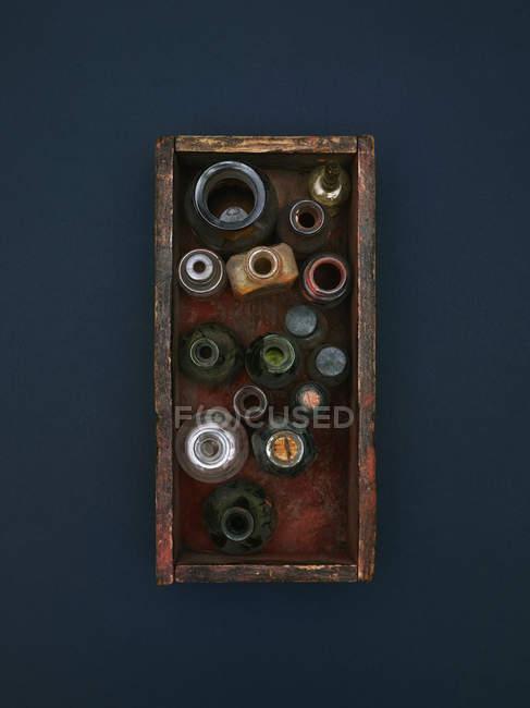 Прямо над кадром старых бутылок и банок в ящике — стоковое фото