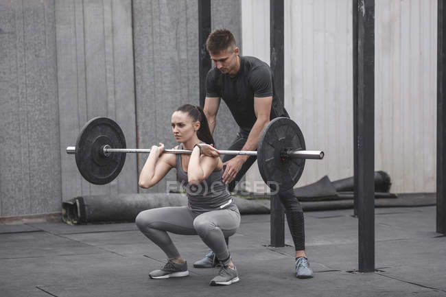 Male instructor assisting young woman crossfit training at gym — Stock Photo