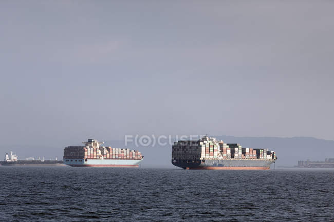 Container ships moored on sea against sky — Stock Photo