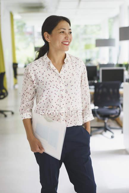 Donna di affari sicura che tiene file stando in ufficio creativo — Foto stock