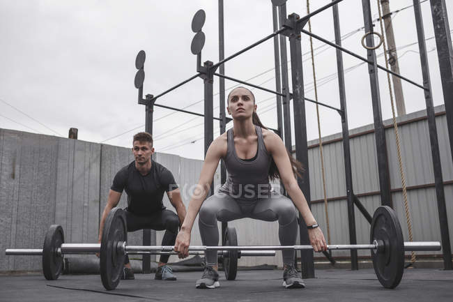 Male and female athletes exercising with barbells during crossfit training — Stock Photo
