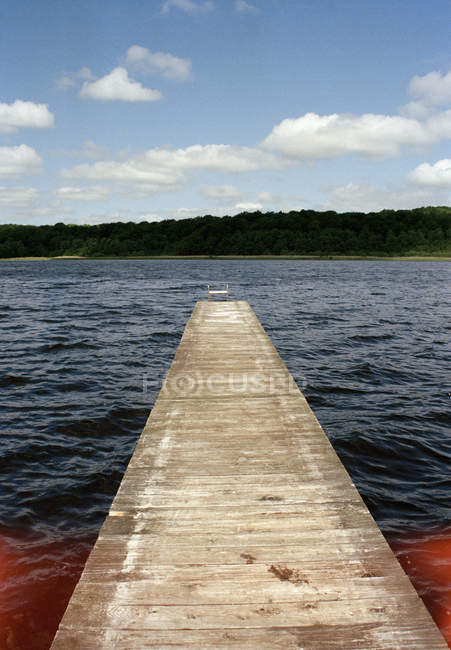 Jetty leading into lake at sunny country — Stock Photo
