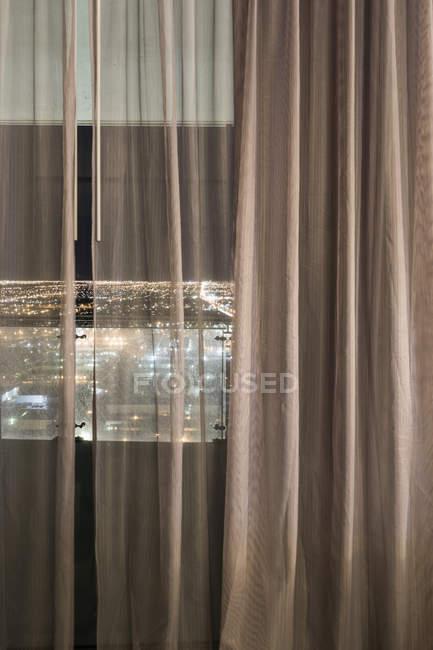 Ve a ciudad iluminada vista a través de cortinas sobre la ventana en la noche - foto de stock