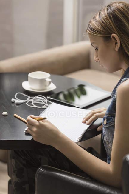 Молода жінка навчається під час за кавою в бібліотеці — стокове фото