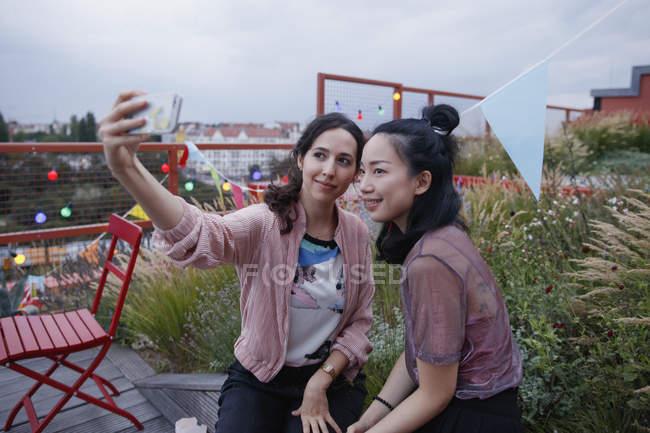 Donne sorridenti scattare selfie con smartphone sul patio — Foto stock