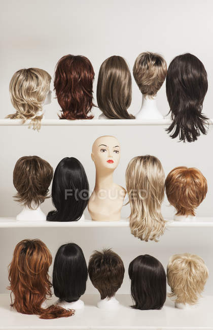 Mannequin heads amidst various wigs on shelves — Stock Photo