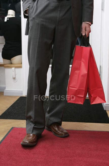 Low section of man in formal attire holding two shopping bags — Stock Photo