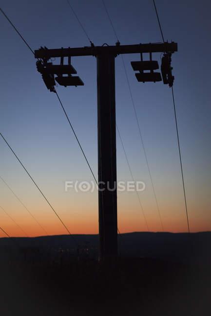 Silhouette eines Strommasten auf dem Feld über dem Himmel bei Sonnenuntergang im Hintergrund — Stockfoto