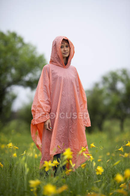 Woman wearing raincoat standing amidst yellow flowering plants in rainy season — Stock Photo