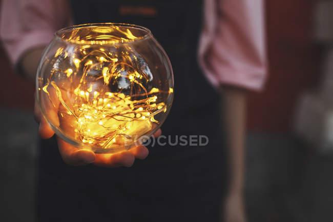 Abdomen de la jeune fille tenant des guirlandes lumineuses en bol en verre — Photo de stock
