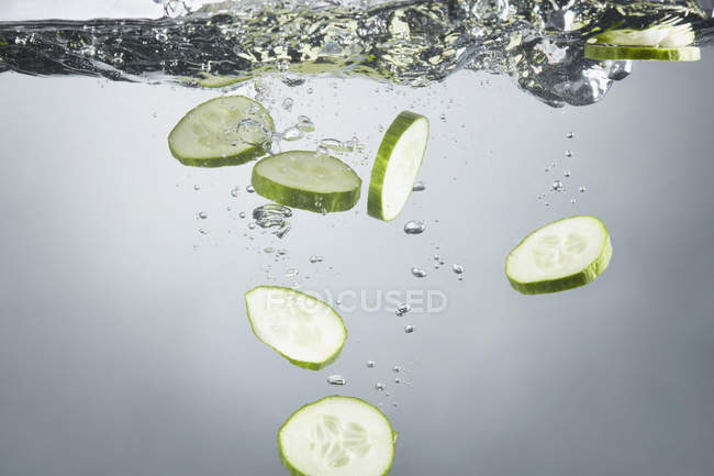 Vue rapprochée des tranches de concombre dans les éclaboussures d'eau — Photo de stock